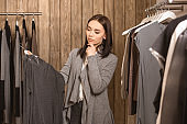 Young adult woman with ponder face in stylish store
