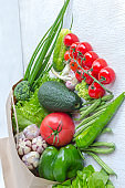 Healthy food in a paper bag of different vegetables on white background. Top view