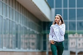Young famale calling on a smartphone and walking on street. Attractive businesswoman talking by phone. Office building and in the Business District Background. Technology internet and happy people concept