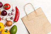 A set of products for diet food. Brown paper bag with vegetables. View from above. White background