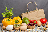 A set of products for healthy eating. Paper bag with walnuts, chickpeas, beans, lentils, yellow and red peppers, tomatoes, avocado on a gray background.