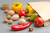 A set of products for healthy eating. Paper bag with walnuts, chickpeas, beans, lentils, yellow and red peppers, tomatoes, avocado on a gray background. Organic food. Top view
