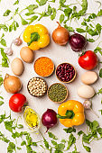 A set of vegetables for a healthy diet, yellow and red peppers, lentils and beans, chickpeas, avocado, tomatoes, onions, garlic. Top view, white background.