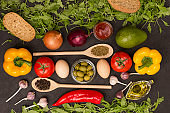 A set of vegetables for a healthy diet, yellow and red peppers, tomatoes, onions, garlic, eggs, olives, rocket,  spinach. Two wooden spoons. Top view, black background