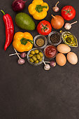 A set of vegetables for a healthy diet, yellow and red peppers, tomatoes, onions, garlic, eggs, olives, rocket,  spinach.  Top view, black background. There is a place for text