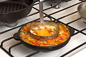Vegetables stewed in pan on stove,  form for frying eggs in pan