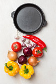 """Frying pan. A set of vegetables for a healthy diet, yellow and red peppers, tomatoes, onions, garlic. Top view, white background. """"n"""