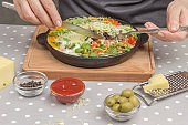 Stewed eggs and vegetables in a pan, shakshuka for breakfast. Hands holding a fork and knife. Cheese, grater, olives, peppers on the table. Gray Polka Dot Background