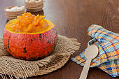 Pumpkin porridge in an orange pumpkin on burlap. Wooden spoon and napkin in an orange cell on the table