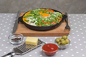 Stewed eggs and vegetables in a pan, shakshouka for breakfast. Cheese, grater, olives, peppers on the table. Gray Polka Dot Background