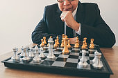 Businessman leadership playing chess and thinking strategy plan about crash overthrow the opposite team and development analyze for successful of corporate