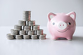 Images of stacking coins pile and pink smiling piggy bank to growing and savings with money box, Saving money for future plan and retirement fund concept