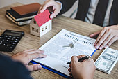 Estate agent giving house and keys to client after signing agreement contract real estate with approved mortgage application form, concerning mortgage loan offer for and house insurance