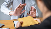 Anti bribery and corruption concept, Business man refusing and don't receive money banknote in envelope offer from business people to accept agreement contract of investment deal