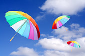 Three rainbow umbrellas flying on a blue sky. Windy and rainy weather metaphor.