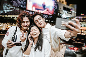 Thai gangster having fun with city life after working,aking a selfie with a phone stock photo