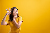 Happy woman showing OK gesture isolated on yellow background