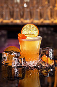 Whiskey Sour alcohol cocktail with orange slice and ice cubes on black mirror background made by man bartender