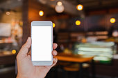 Phone in hand on a blurred background, coffee shop