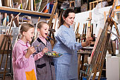 Skillful woman teacher showing her skills during painting class at art studio