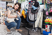 Glad woman holding dog and choosing clothes