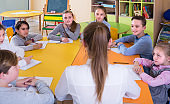 Nice teacher and children sitting at table
