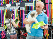 Cheerful man with dog looking bowl in pet store