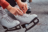 Young couple preparing to a skating. Close-up photo of their hands tying shoelaces of ice hockey skates in the locker room
