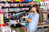 Young woman customer choosing plastic toilet in pet store