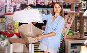 woman customer choosing portable carrier box in pet store
