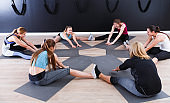 Young females in circle during yoga class