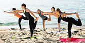Young positive women exercising yoga poses on sunny beach