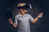 Blonde boy dressed in a white t-shirt playing ping-pong with a virtual reality glasses. Isolated on dark textured background.