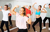 Teenage girl practicing dance with group