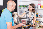 female talking to a  buyer with dog