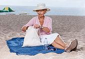 Elderly woman relaxing on beach