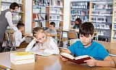 School friends reading books in library