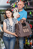 Young family with dog choosing carrier box