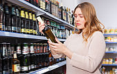 Portrait of nice woman buying bottle of wine