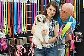Happy family couple with dog  choosing new bowl