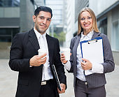 Businesswoman and her partner are standing with folder and coffee