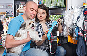 Couple customers with dog choosing clothes for dog