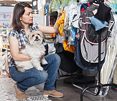 Nice woman holding dog and choosing clothes