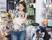 Smiling woman holding dog and choosing clothes