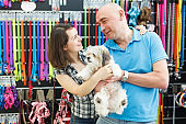 smiling couple with dog looking for collars