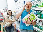 man with purchases talking on mobile