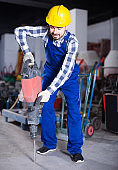 working man practicing his skills with pneumatic drill at workshop