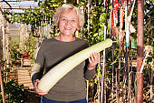 Senior woman taking long zucchini