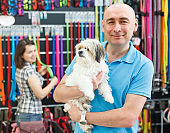 Positive man with dog in pet store