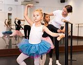 Ballet trainer teaching two little girls